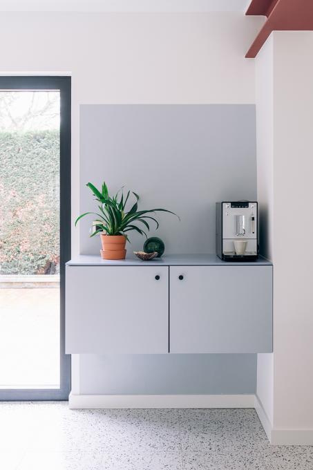 Een grijs kleurvlak in de hoek van de kamer geeft een speels, maar elegant effect