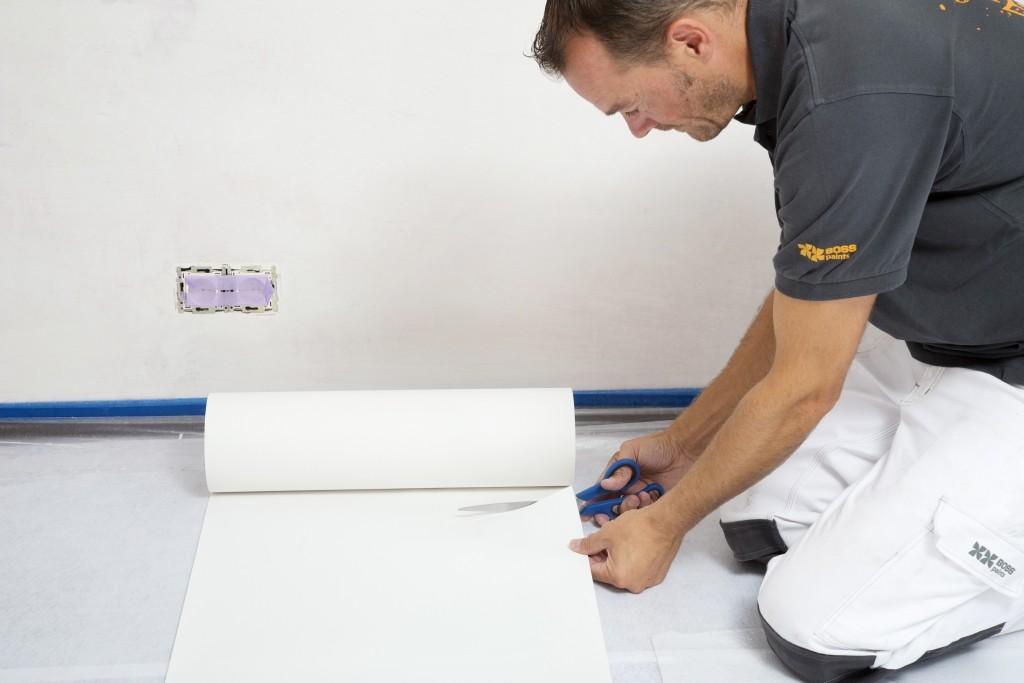 Behangen met vliesbehang: snij enkele stroken vliesbehang op maat