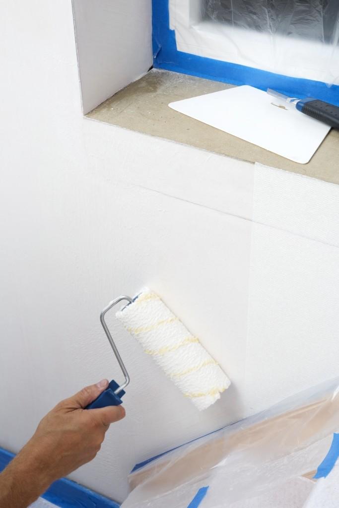 Behangen met vliesbehang: breng de lijm aan op de muur met een langharige rol